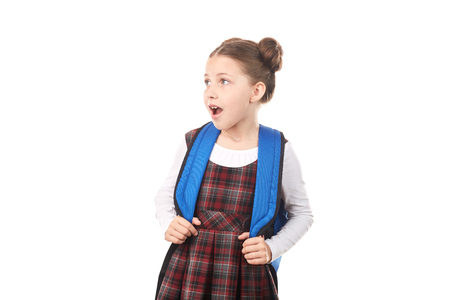 Portrait of shocked girl in school uniform with backpack against white background