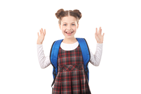 Portrait of excited girl in school uniform with backpack against white background Reklamní fotografie