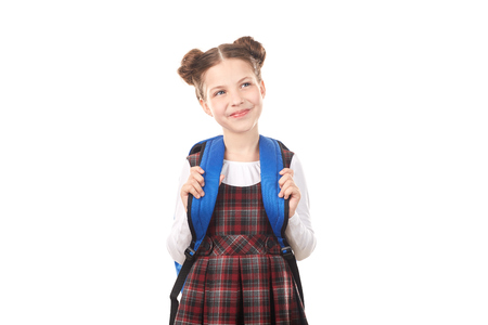 Portrait of cute girl in school uniform with backpack dreaming against white background