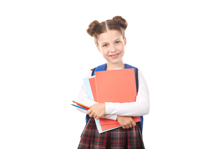 Portrait of girl in school uniform with backpack holding textbooks and pencils against white background Imagens