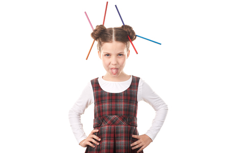 Portrait of cute girl in school uniform with pencils in her hair bun against white background Stock Photo