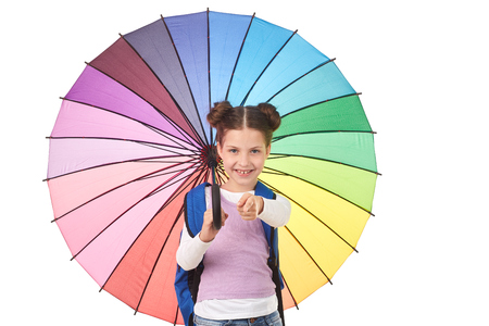 Studio portrait of elementary schoolgirl holding open colorful umbrella