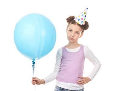 Studio portrait of little girl wearing birthday hat posing against white background