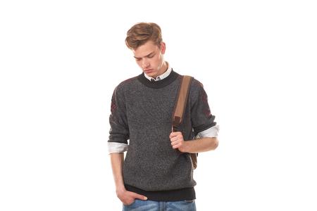 バックパックとカジュアルな服でハンサムな大学生の男の子のスタジオ ポートレート