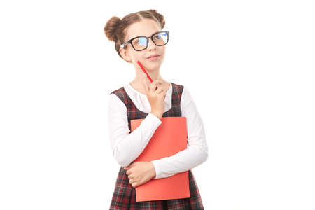 Portrait of girl wearing eyeglasses and school uniform standing against white background