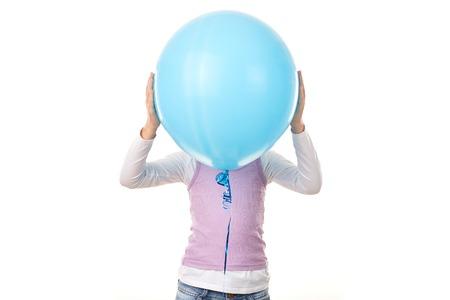 白い背景の青い風船の後ろに隠れている少女のスタジオ ポートレート 写真素材