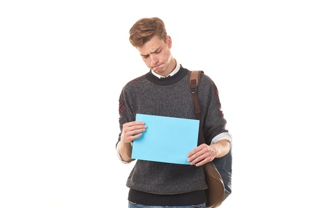 Portrait of teenage student holding blank paper against white background