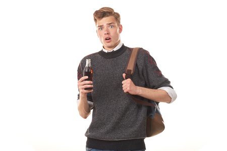 Studio portrait of teenage student drinking cola from glass bottle