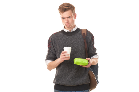 Handsome college boy holding lunchbox and paper cup of coffee Stock Photo