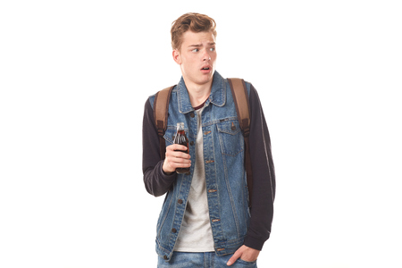 Portrait of handsome college boy holding glass bottle of cola