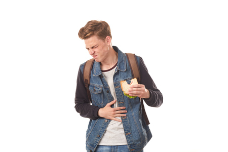 Portrait of student feeling disgust after eating rotten sandwich