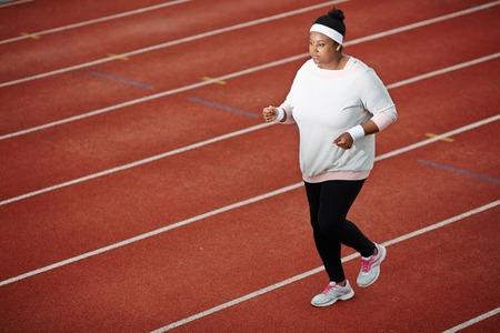 결정된 과체중 아프리카 여자 달리기 트랙에서 조깅 스톡 콘텐츠