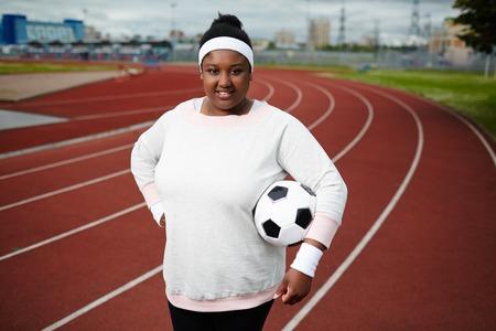 肉付きの良い女性が陸上競技場でサッカー ボールとポーズ