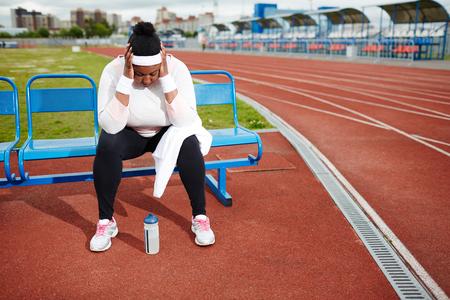 ぽっちゃり女性の陸上競技場で厳しいトレーニング後の回復
