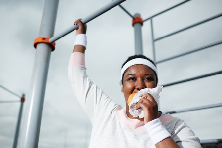 Plump African woman eating unhealthy burger while practicing pull-up exercise