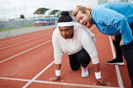 Personal trainer motivating overweight woman preparing for run competition