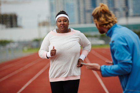 Determined plus-size woman running on track