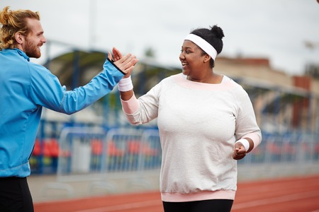 Happy plus-size woman giving high five to her personal trainer