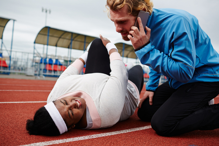 Plump woman lying on running track, her trainer calling emergency service