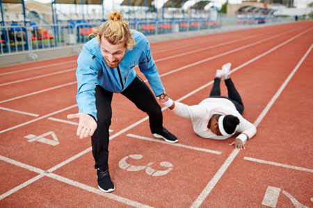 Sport coach dragging exhausted plump client towards finishing line