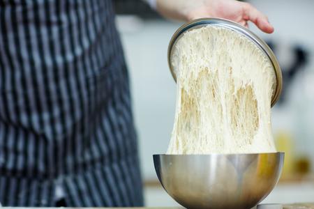 Baker checking sourdough starter in metallic bowl 版權商用圖片
