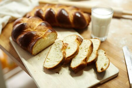 Fresh sliced bread on wooden board and glass of fresh milk near by