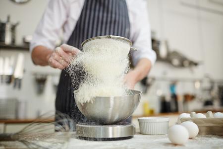 Baker sifting wheaten flour into bowl while preparing dough Фото со стока
