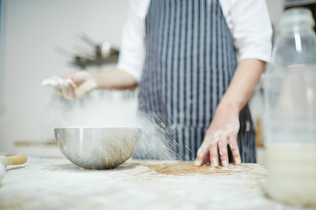 Chef in uniform sprinkling wheaten flour over workplace Stock Photo