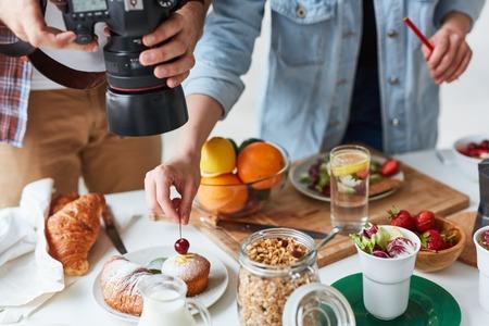 그의 조수 그를 돕는 동안 테이블에 음식을 촬영하는 사진 작가 스톡 콘텐츠