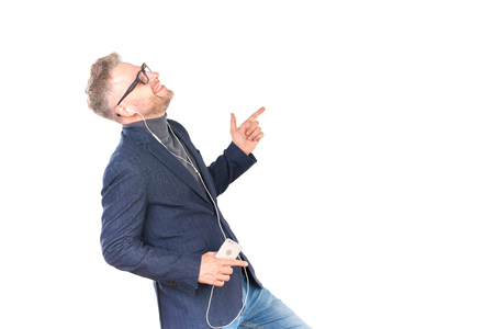 Middle adult man in eyeglasses listening to music on smartphone through earphones