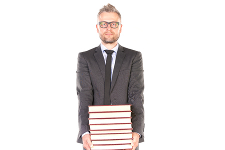 Portrait of middle-aged man in suit holding heap of books