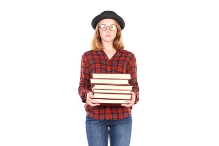 Portrait of female teenage student in hat holding stack of books