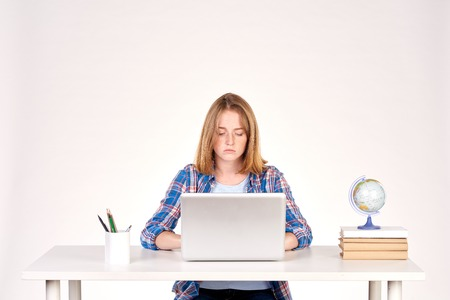 Portrait of teenage red-haired student sitting at desk Stock Photo