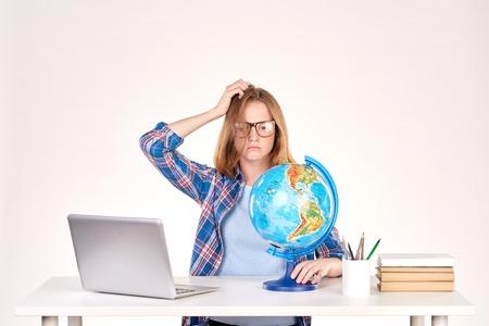 Portrait d'étudiante assis au bureau et à l'aide de globe Banque d'images - 83735760