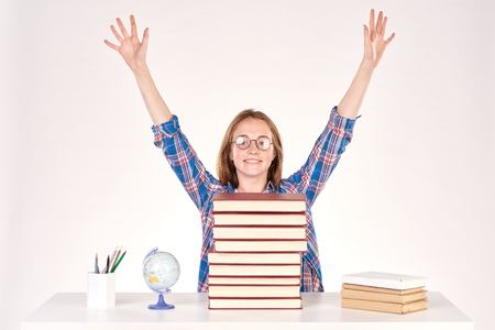 Beautiful teenage schoolgirl sitting at desk with stack of books on it Stock Photo