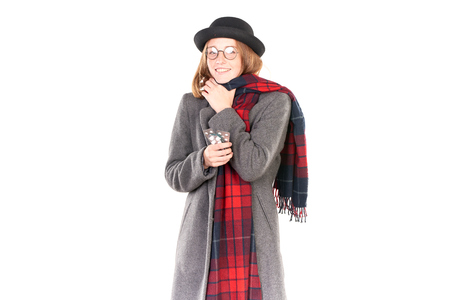 Portrait of teenage girl wearing gray coat, hat and scarf feeling flu symptoms Stock Photo