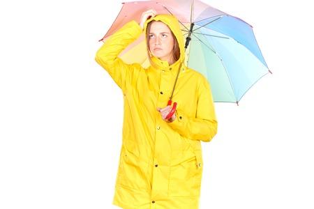 Studio portrait of teenage girl wearing yellow raincoat and holding open colorful umbrella isolated on white Stock Photo