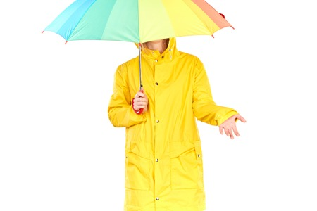 Studio portrait of teenage girl wearing yellow raincoat and holding open colorful umbrella isolated on white Stock Photo