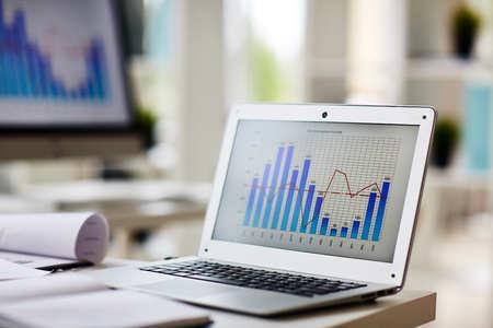 Laptop met grafiek op zijn vertoning op het werk van econoom Stockfoto