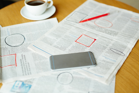 Newspaper with highlighted vacancy adverts, smartphone, cup of coffee and pen on table