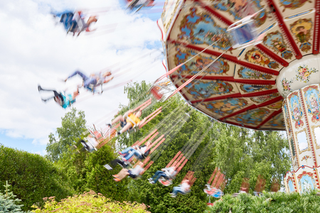 Children swinging on caroussel in theme park on weekend Stok Fotoğraf