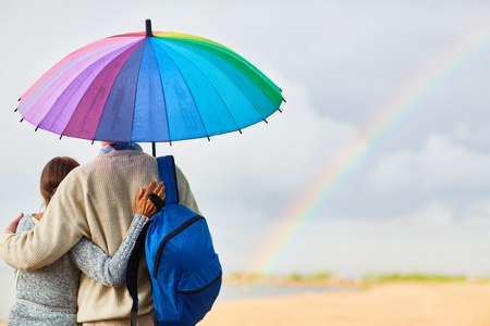 Back view of tourists with backpack standing under colorful umbrella in rural environment Stock Photo