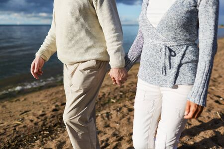 Aged couple holding by hands during walk on sandy beach in the evening Imagens - 83890285
