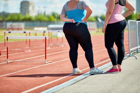 Two plump friends in sportswear standing on racetrack of stadium