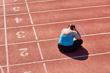 Frustrated over-sized woman sitting on racetrack and crying after training Stock Photo