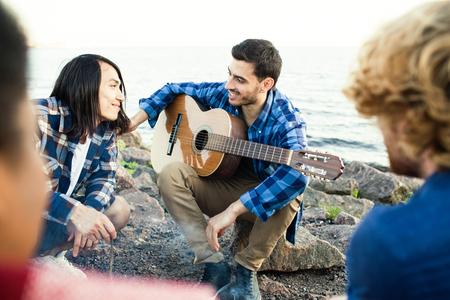 Guys relaxing by seaside