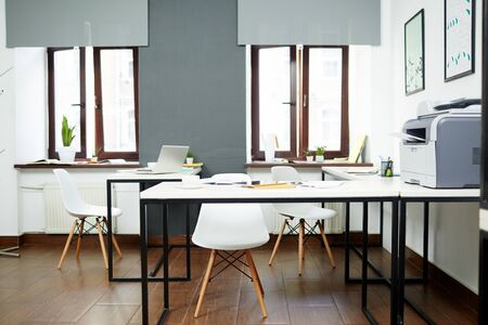 Modern kantoor met verschillende werkplekken, stoelen en benodigdheden op bureaus Stockfoto