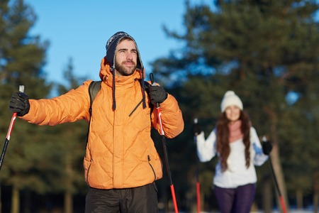 Young sporty couple of skiers having trip in winter forest