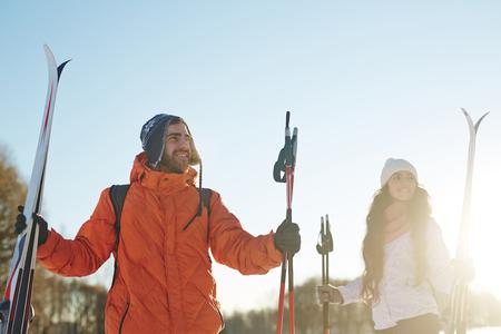 晴れた冬の日に農村環境で週末を過ごすスキーヤーのカップル