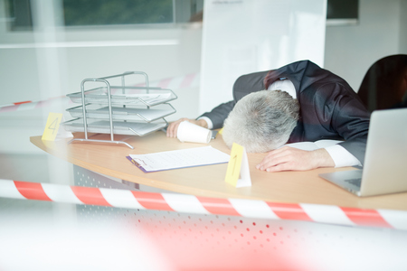 Crime scene: lifeless mature entrepreneur in classic suit lying on office desk, view through panoramic window